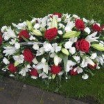 Coffin spray of red roses and white flowers